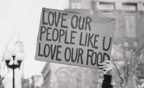 Girl holds poster that reads: Love Our People Like U Love Our Food.